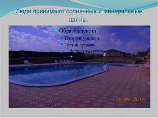 Люди принимают солнечные и минеральные ванны.