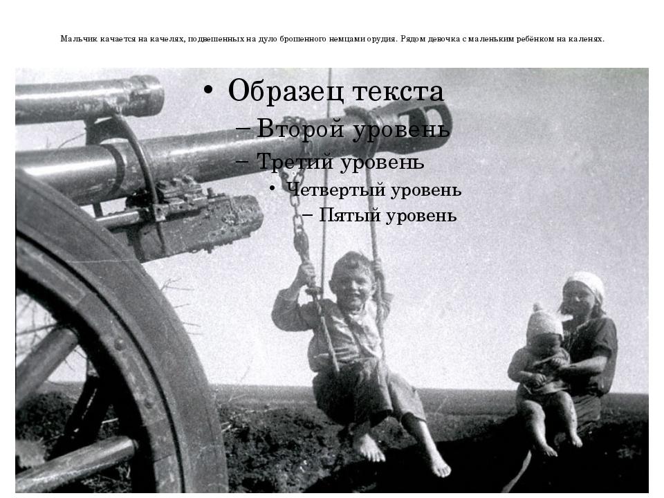 Мальчик качается на качелях, подвешенных на дуло брошенного немцами орудия. Р...