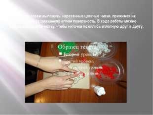 Тонким слоем выложить нарезанные цветные нитки, прижимая их пальцами на смаз