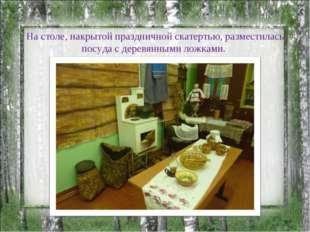 На столе, накрытой праздничной скатертью, разместилась посуда с деревянными л