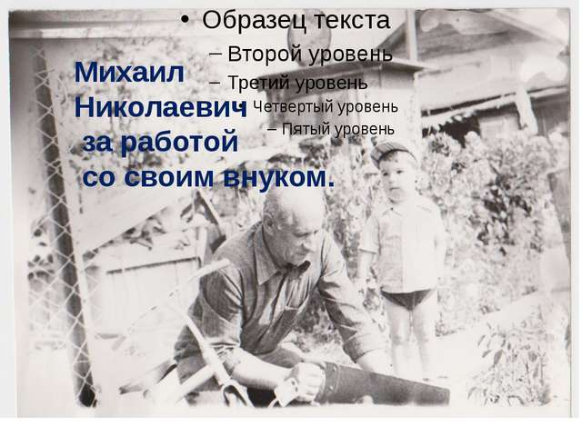Михаил Николаевич за работой со своим внуком.