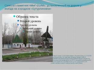 Самолёт-памятник «МиГ-21УМ», установленный на дороге у въезда на аэродром «Бу