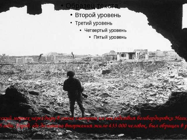 Американский морпех через дыру в стене смотрит на последствия бомбардировки...