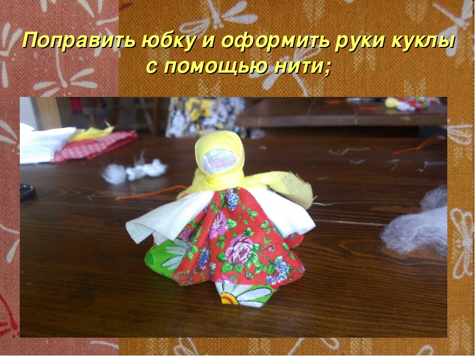 Поправить юбку и оформить руки куклы с помощью нити;