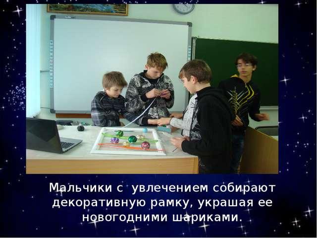Мальчики с увлечением собирают декоративную рамку, украшая ее новогодними ша...
