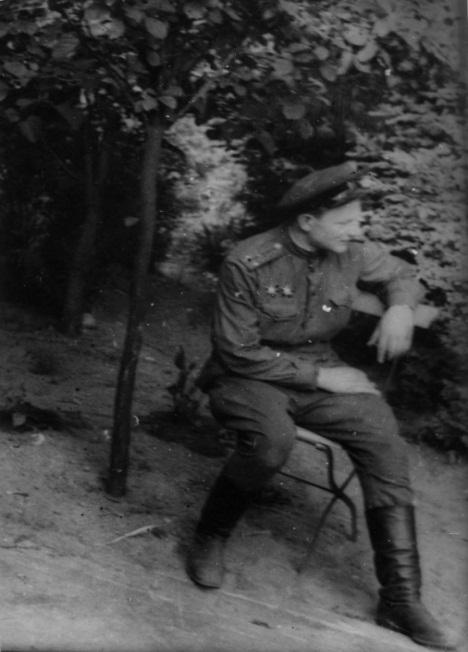 Старший лейтенант П.А. Крюков, сидящий на садовом стуле