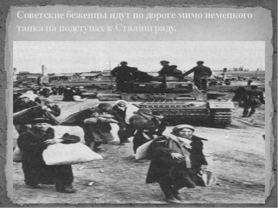 Советские беженцы идут по дороге мимо немецкого танка на подступах к Сталинг...