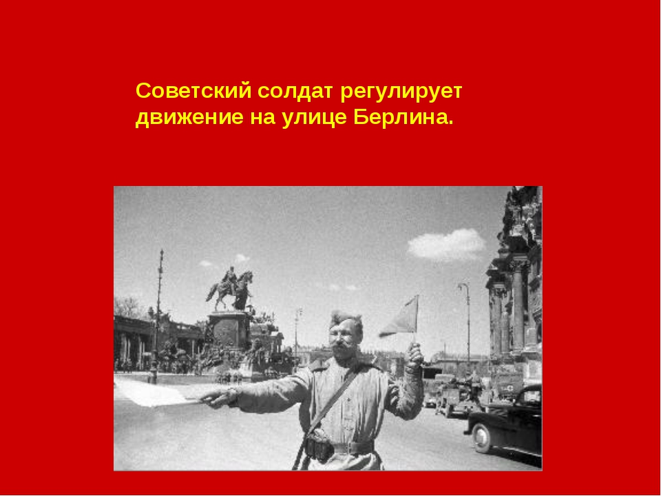 Советский солдат регулирует движение на улице Берлина.