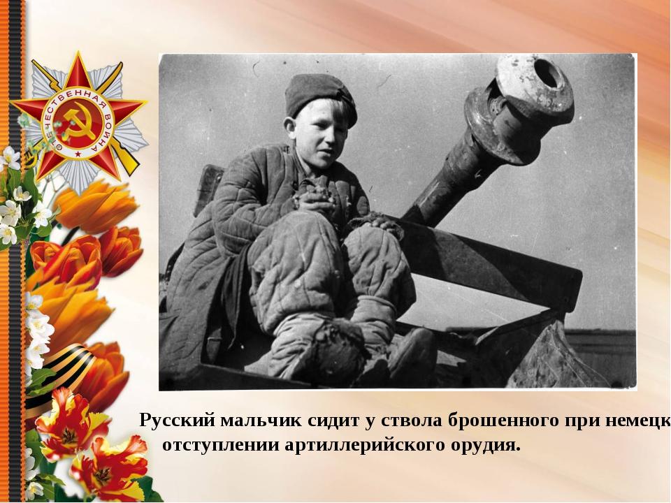 Русский мальчик сидит у ствола брошенного при немецком отступлении артиллерий...