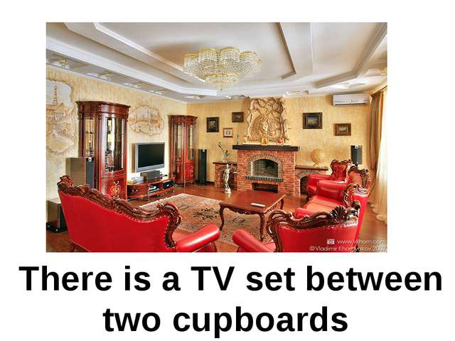 There is a TV set between two cupboards