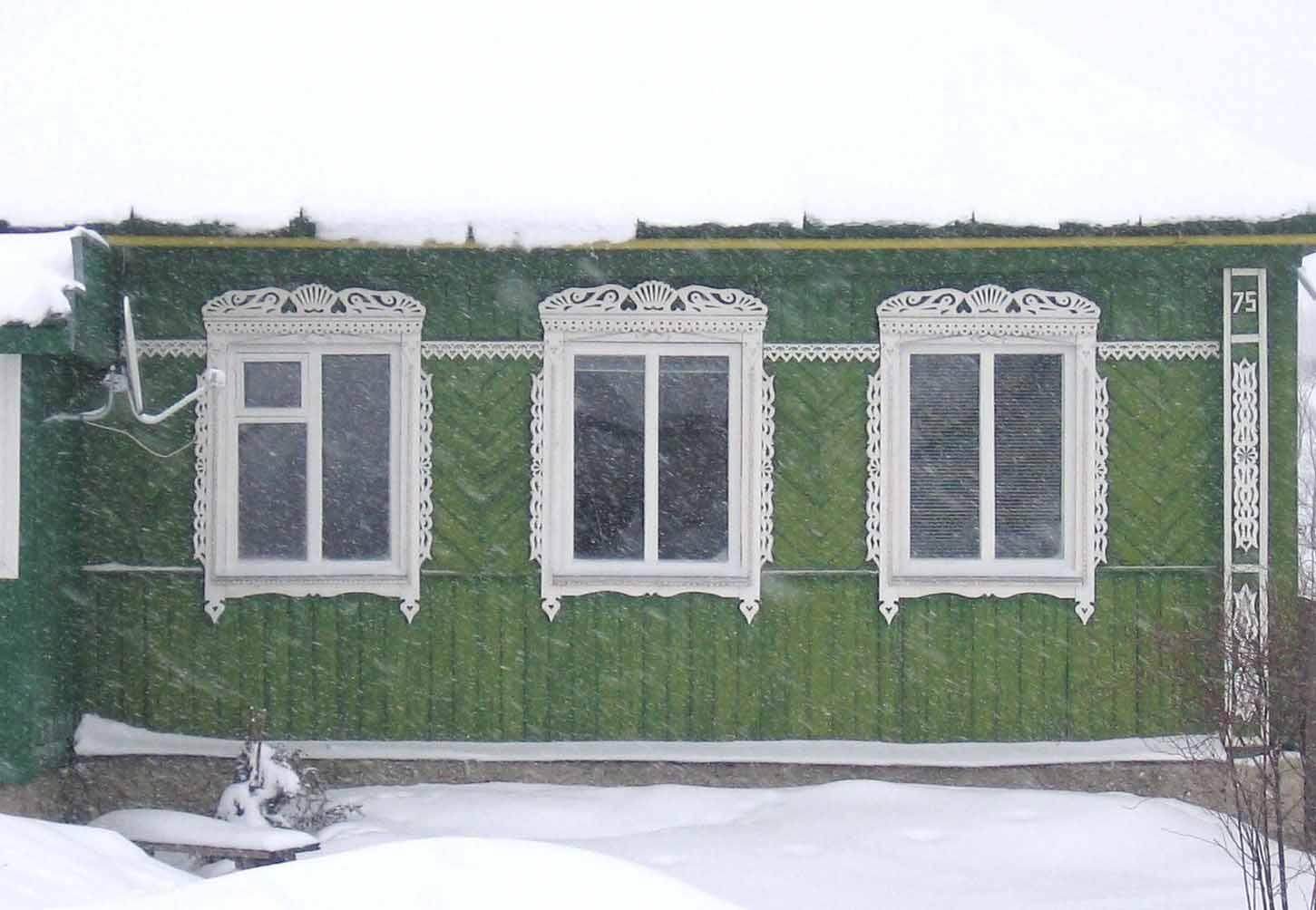 Восстановленный фасад деревенского дома украшенного прорезной резьбой