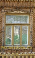 Фотография современных резных наличников с глухой резьбой. Без покраски резьба совершенно потерялась на дощатом фасаде дома.